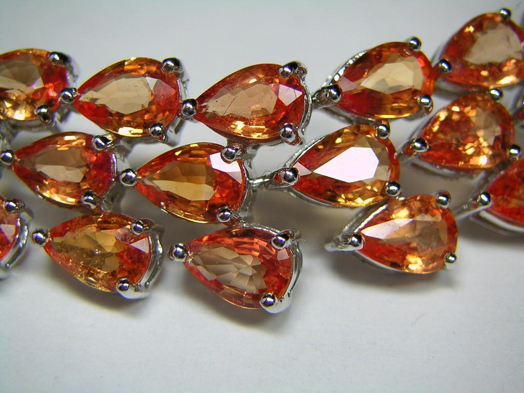 Die Farbe der orangen Saphire im Armband ist auf Beryllium-Diffusionsbehandlung zurückzuführen