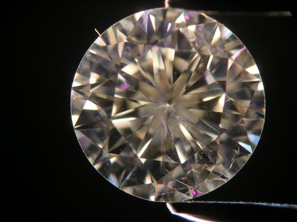 Diamant im Mikroskop: Rißfüllungen sind an rosafarbigen Reflexen zu erkennen