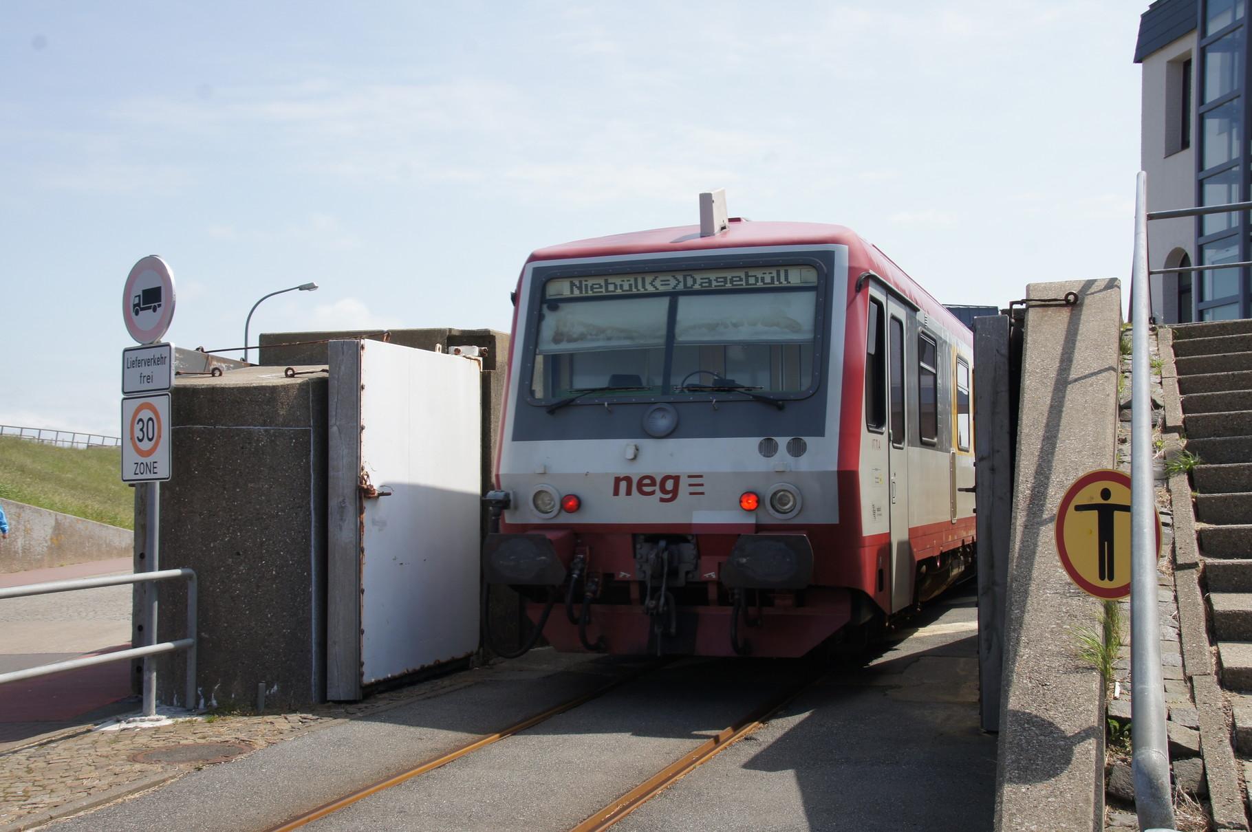 Der Zug durchfährt das Tor durch den Deich in Dagebüll.