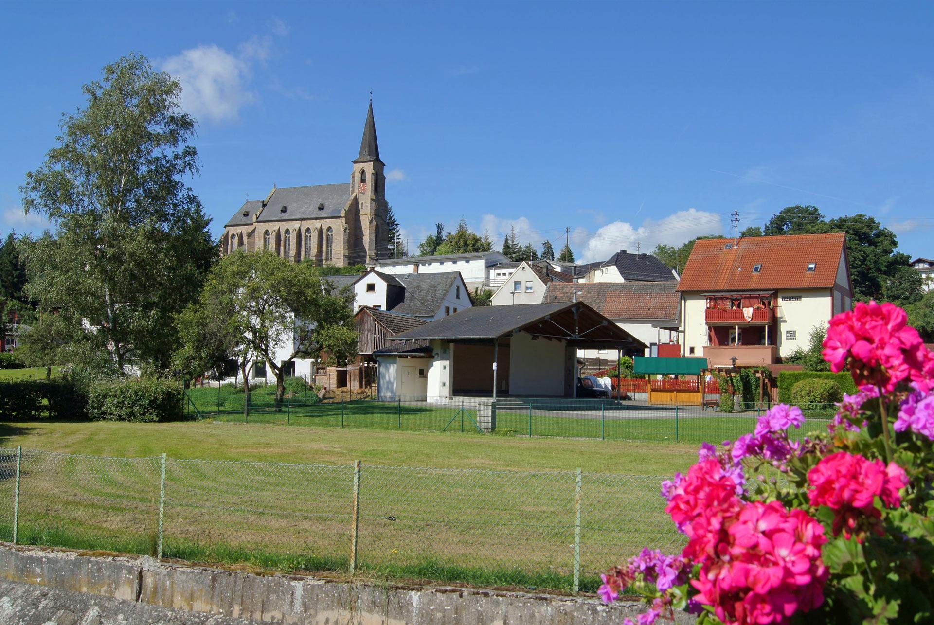 Blick von der Brücke auf Dorfplatz und Kirche