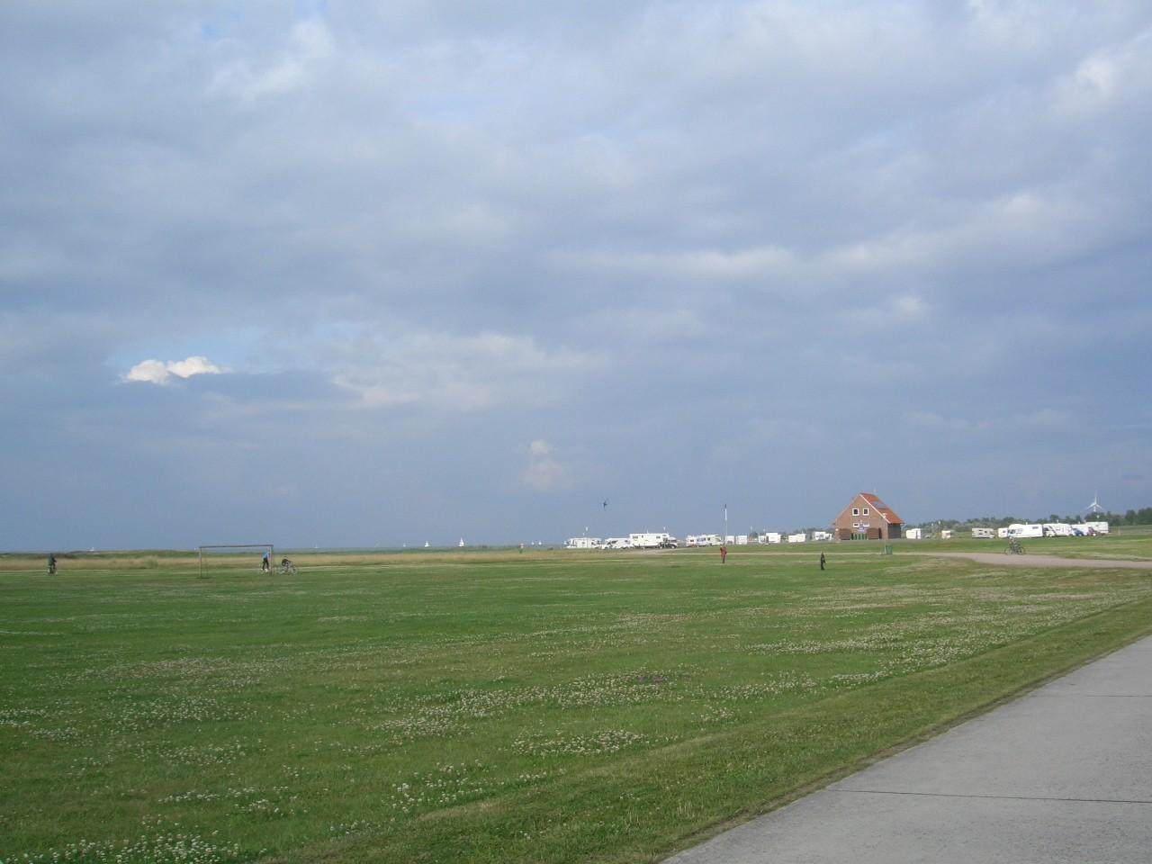 Weites flaches Land mit Stellplatz und Meer im Hintergrund