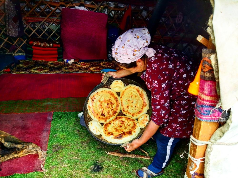 Kyrgyz Nomad woman baking a Nan(bread)in the big pot,inside of the Boz-yui (yurt)