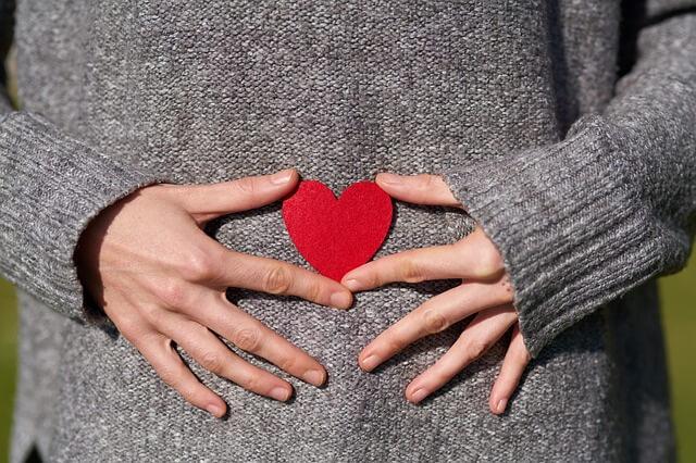 Frau mit grauem Pullover hält ein rotes Herz vor ihren Bauch