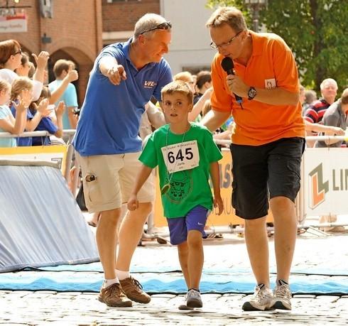 Die Medaille für Sieger Jarle Ehrhardt im Bambini-Lauf gab's schon im Ziel vom Veranstaltungschef Matthias Meyer (li.) und Moderator Jens Wiebusch (re.)