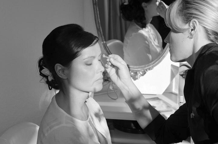 Eine Kosmetikerin schminkt eine Braut.
