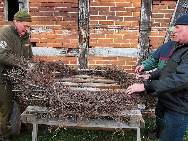 Ein Kranz wird, noch am Boden, auf der Holzunterkonstruktion befestigt