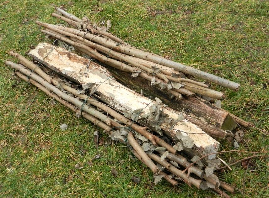 Buschvasen - eine Alternative zur Holzgestellkonstruktion. Zwei mit Drähten verbundene Zweigbündel werden über den Dachfirst gelegt