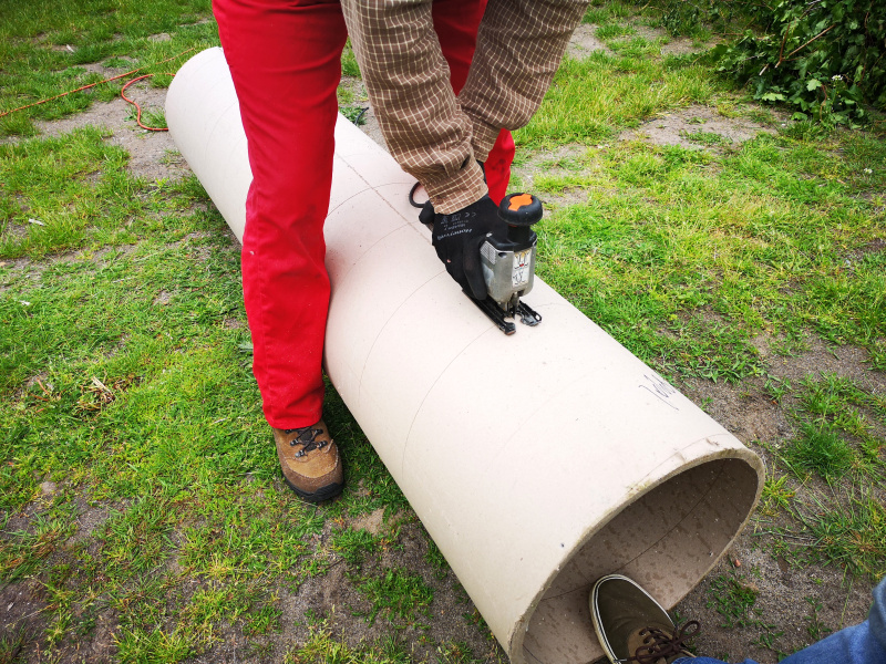 Eine riesige Papprolle wird in zwei Teile gesägt...