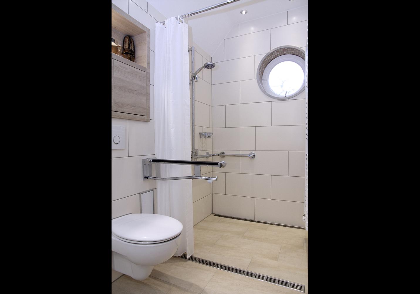 Im Bereich des Duschvorhangs befindet sich eine zweite Edelstahlrinne.