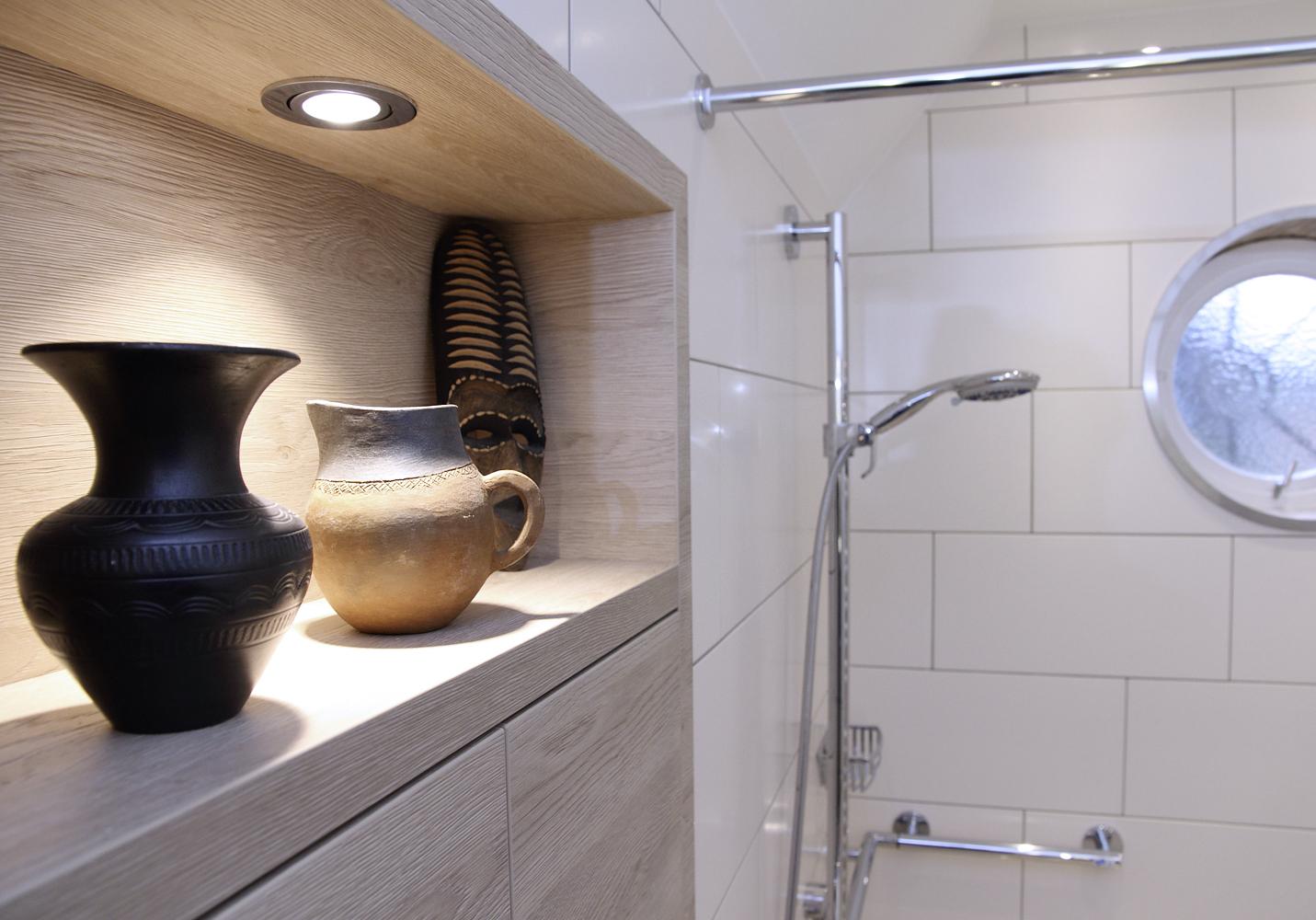 Beleuchtetes Einbauregal aus Holz über dem WC mit Ablagefach und Regaltüren.