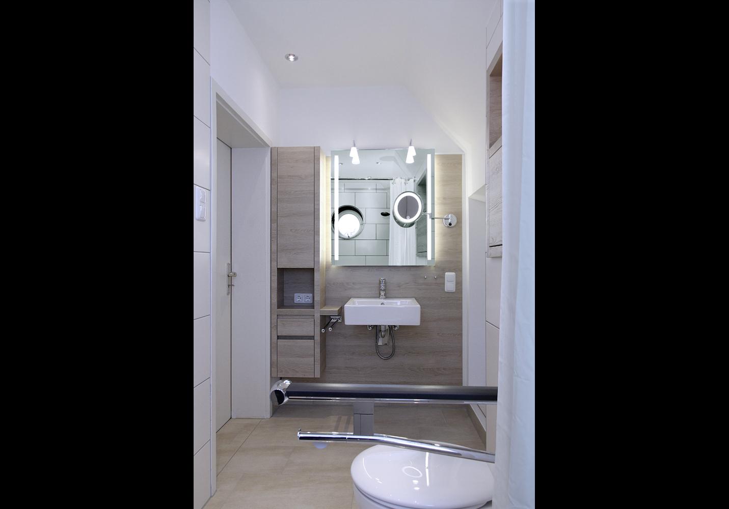 """Spiegel und Waschbecken befinden sich am gegenüberliegenden Raumende. Schrankregal mit Schübe: """"push-to-open"""" und """"softclose""""."""