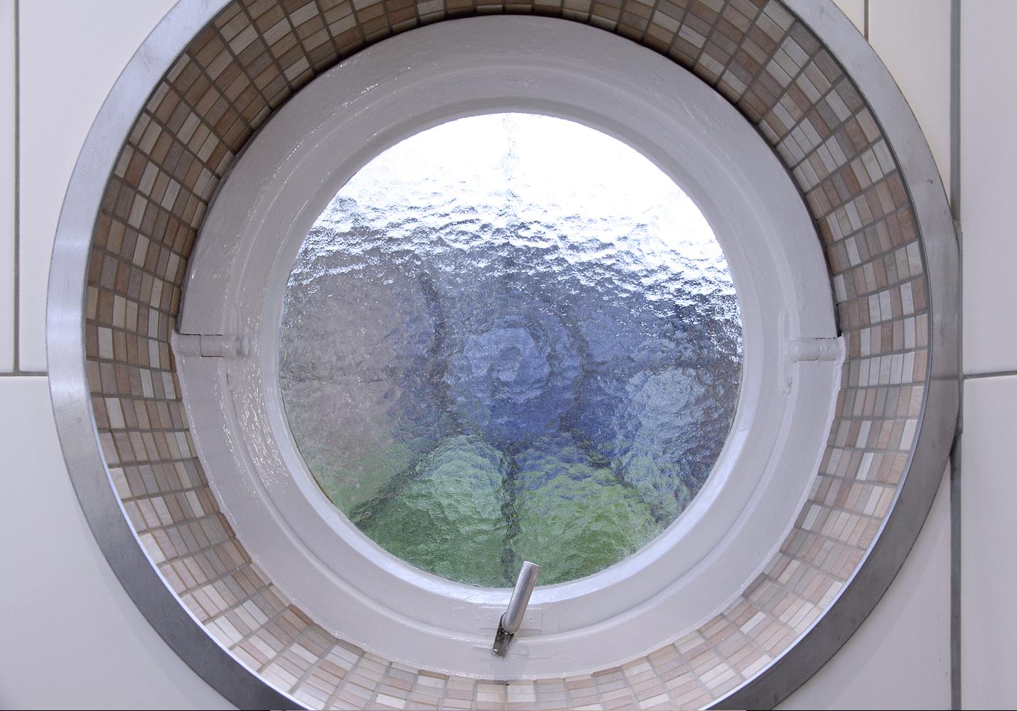Den Abschluss im Übergangsbereich zwischen Mosaikfliesen im Rundfenster und den Wandfliesen bildet ein flacher Edelstahlring.