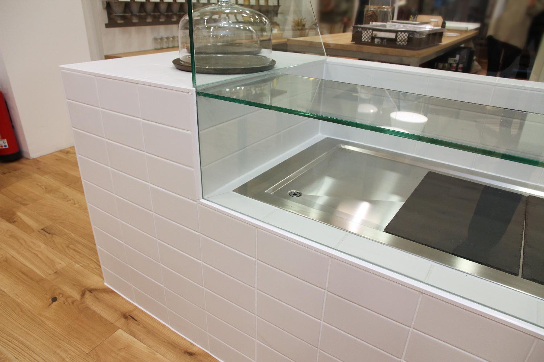 Auf der integrierten Kühlplatte und den Glaseinbauten werden belegte Brote angeboten