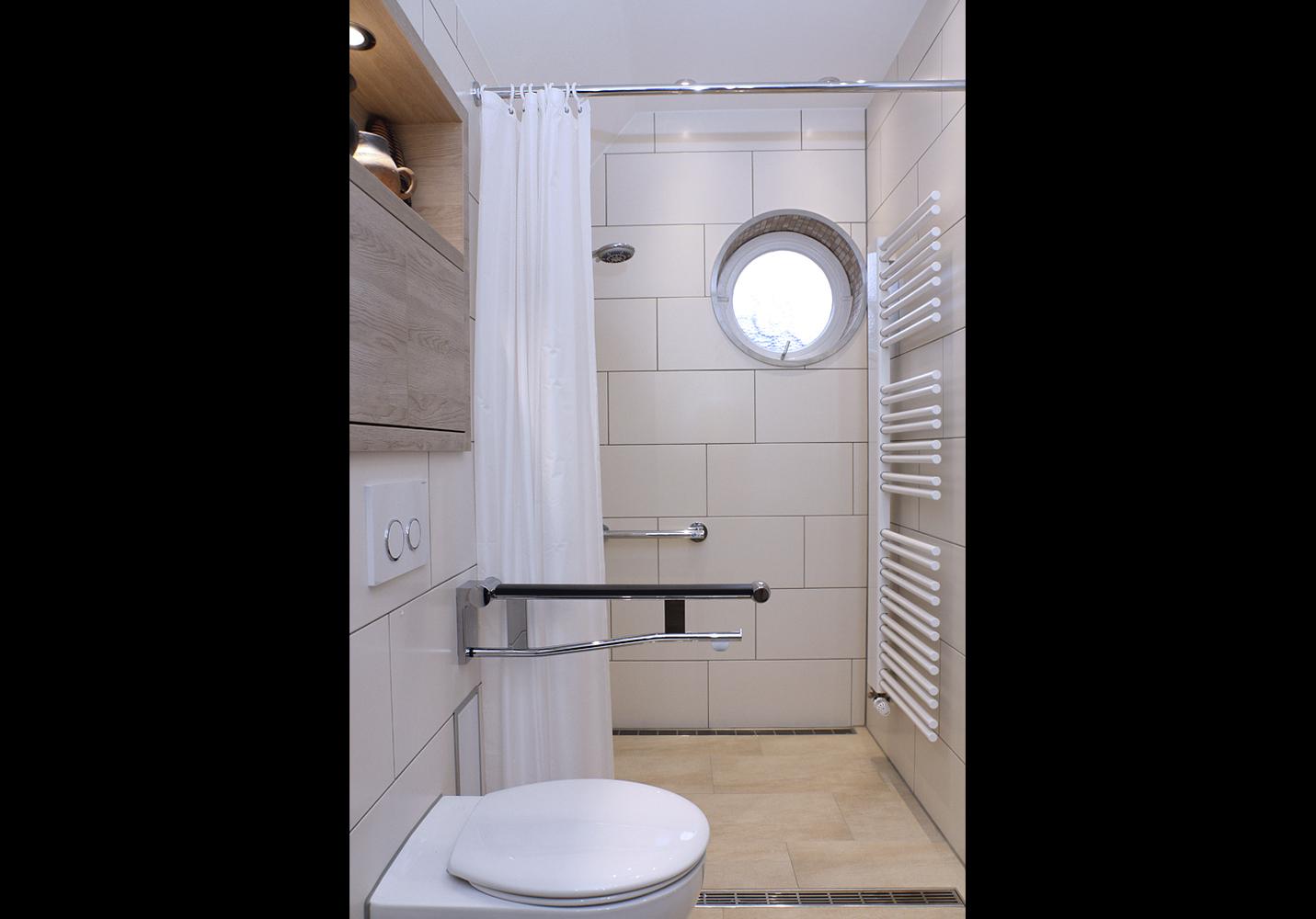 Blick in den gefliesten Duschbereichs mit historischem Rundfenster. WC mit Klapphaltegriff.