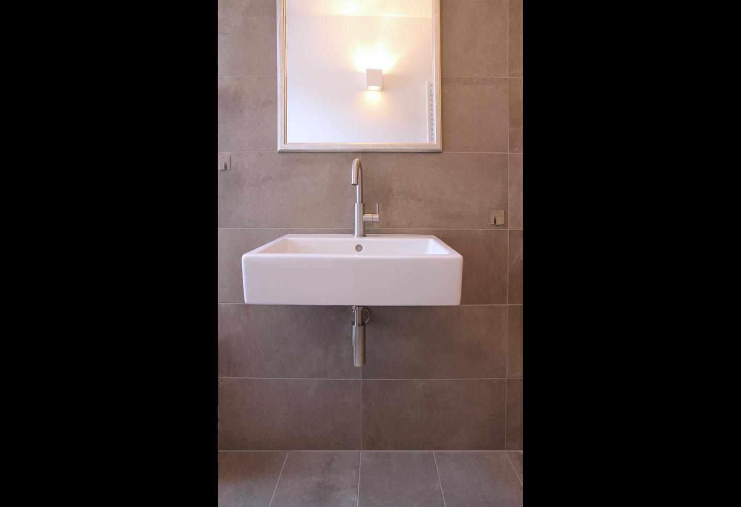 Der Bodenbelag findet seine nahtlose Fortsetzung im Duschbereich.