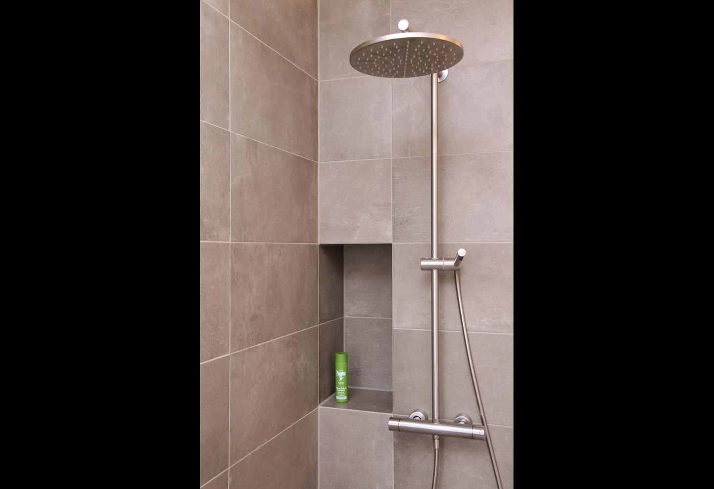 Offener Duschbereich ausgefliestes Fach und stilvolle Stabbrause.