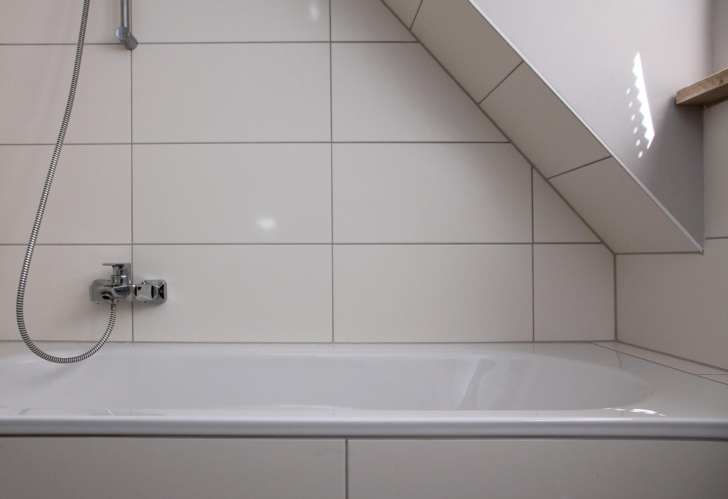 OG: Wandgestaltung mit weissen, schlichten Keramikfliesen 30 x 60 cm.