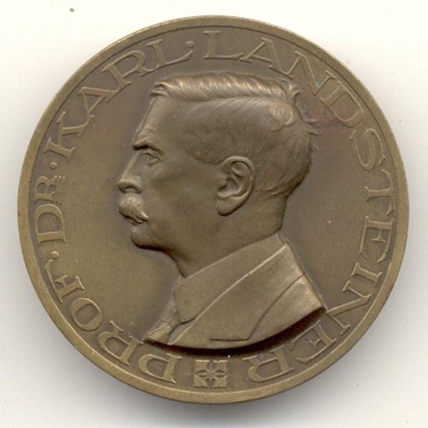 Frente Medalla, Austriaca emitido (20th Century) en honor Prof. Karl Landsteiner (biólogo y médico, Premio Nobel de Medicina 1930, por descubrir los Grupos Sanguíneos ABO, Rh; entre otros. Metal: Bronce de 40,16 mm. Peso: 22,1 gs o 0,777 oz.