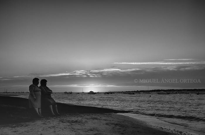 Las carreras han terminado. En un extremo de la playa, algo lejos de donde han tenido lugar, dos sanluqueñas miran coo al desgaire cómo el sol se retira a descansar...