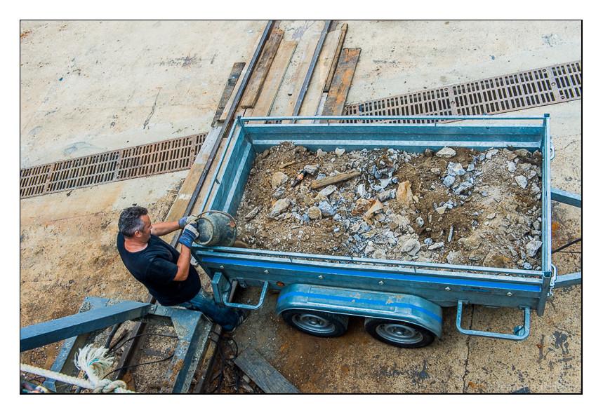 Des mètres cube de gravas sont extirpés de la coque rouillée et percée comme un gruyère
