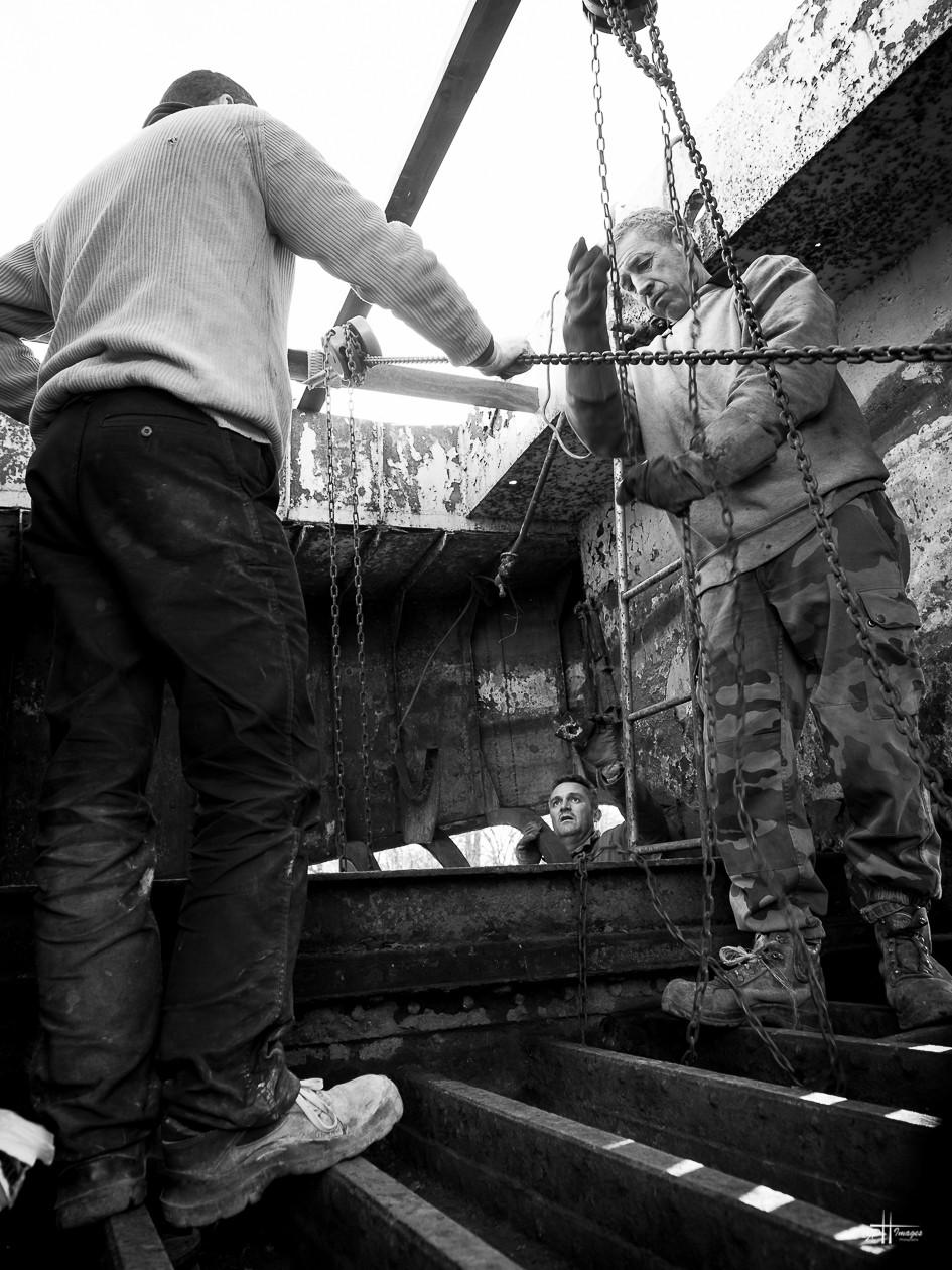 Toutou, Philippe et Laurent dit Lolo rusent de méthodes diverses pour déformer les tôles avant de la souder; ici traction avec des palans et des chaines