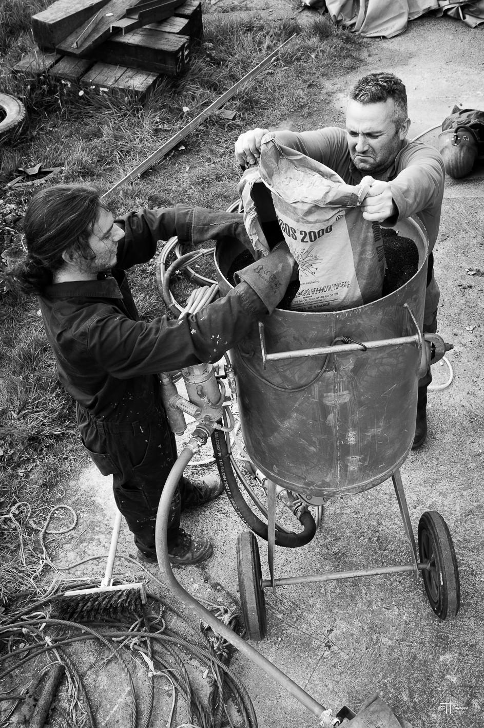Julien et Philippe remplissant la cuve de la sableuse