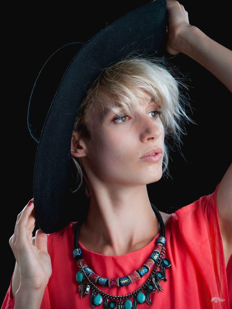 Chapeau noir couvrant ses cheveux blonds baignés dans une  lumières douce