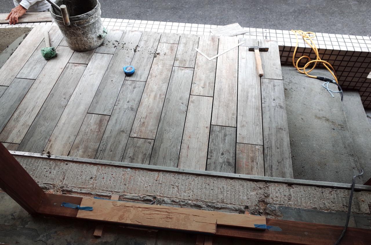 ポーチ部分から階段にかけて、木目のタイルを貼っていきます。