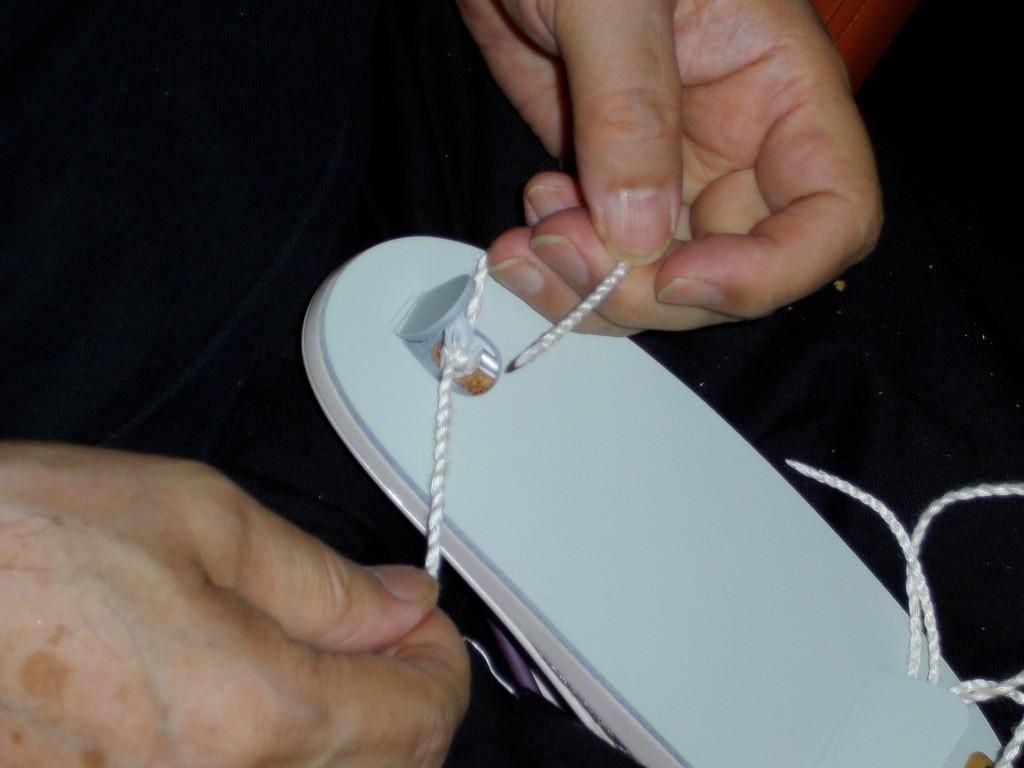 鼻緒の前(前坪)をお客様の足のサイズに調整して結びます。