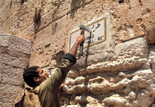 Un soldat israélien efface une inscription en arabe sur le mur des Lamentations, en 1967 MICHA BAR AM / MAGNUM PHOTOS