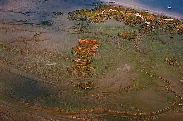 Watt in der Flachwasserzone vor dem Bishorster Sand und rechts liegt ein Segler vor Anker