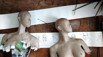 Logo Online Magazin, 2 Papier Skulpturen auf dem Boden liegend mit Pinsel und Papierstreifen
