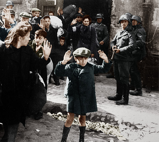 Ein Foto von ungeheurer Symbolkraft: April/Mai 1943 im Warschauer Ghetto. Ein kleiner polnischer Junge, dem die Angst ins Gesicht geschrieben steht, wird mit erhobenen Händen abgeführt. Im Hintergrund hält Bewacher Josef Blösche das Maschinengewehr.