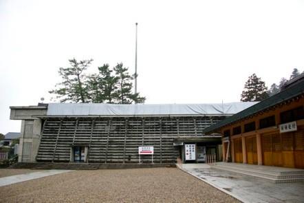 現在の庁の舎 雨漏りの為にシートがかけられている。右は出雲大社の仮拝殿