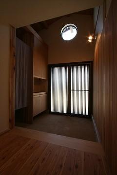 玄関上部を吹き抜け勾配天井とし、アクセントの丸窓を設けた。