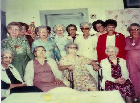 Foothills Events: The Blue Ribbon Circle pictured in the community center with the old quilt (right-hand corner), 1980 1st row: Emily Anderson, Liddia Maiers, Lula Domke, Violet Pipgras 2nd row: Hattie Cheek, Louise Bislerfeldt, Elsie Wruble, ? Olinger, ?