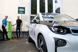 Fahrdienstleiter Frank Kessel (l.) und Fahrer Stefan Meng laden ein Elektro-Fahrzeug am Standort Wilhelmshöher Allee auf. Foto: Uni Kassel.