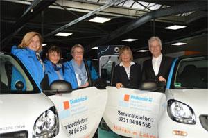 Anne Rabenschlag (Diakonie, 2.v.r.) übernimmt eine smart electric drive-Flotte von Gerd Hewing (smart Center Dortmund)