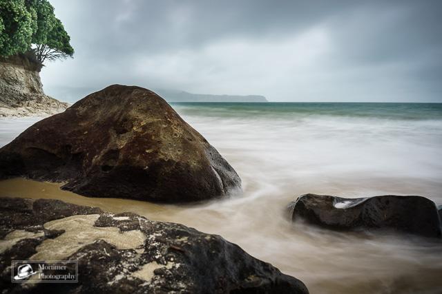 Vom Meer umspülte Steine vor dramatischer Wolkenfront
