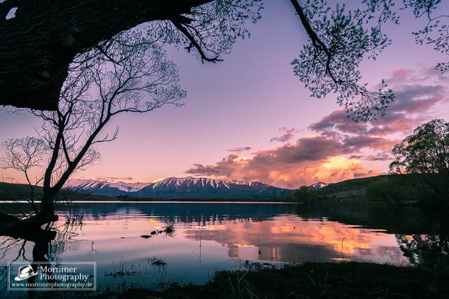 Farbenpracht beim Sonnenuntergang am See vor Bergkulisse