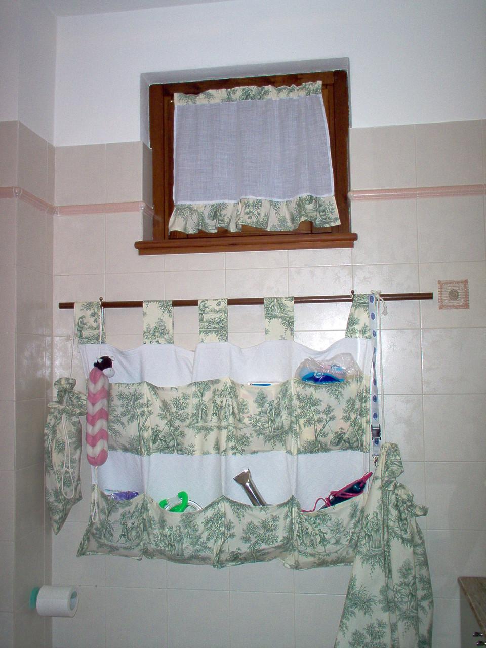 Il pannello porta oggetti è indispensabile per tenere in ordine il bagno. In questo caso abbiamo aggiunto gli utilissimi sacchi per la biancheria e la tenda realizzata in coordinato