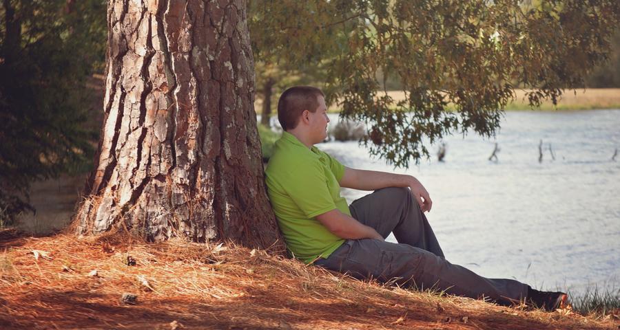 Ein Mann sitzt unter einem Baum
