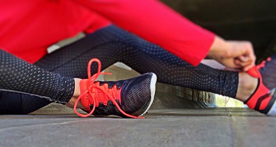 Das ideale Training, Frau mit Jogginghose zieht sich gerade die Turnschuhe an