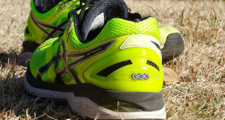 Training bei Hitze, Gelbe Turnschuhe auf vertrocknetem Rasen
