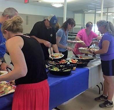 Parent volunteer Audra Knoedler (pink shirt) replenishes a food station as teachers enjoy the buffet.