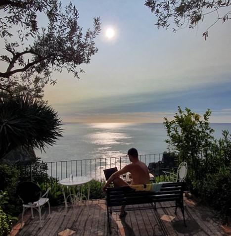 freaky finance, Sizilien, Taormina, Urlaub, Aussicht auf das Meer, Meerblick, Mann auf einer Bank mit PC