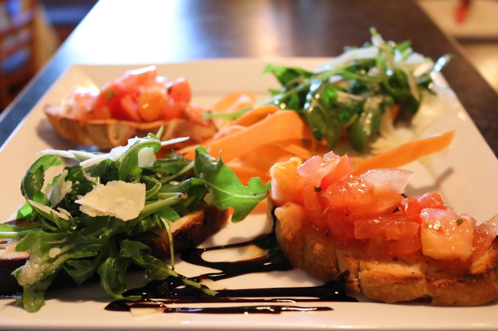 Bruschetta aus hausgebackenem Brot mit Tomaten, Oregano und Olivenöl & mit Rucola und Parmesanscheiben