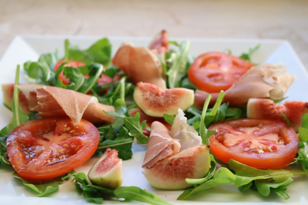 Frische Feigen auf einem Rucolabett mit Tomatenscheiben und Parmaschinken