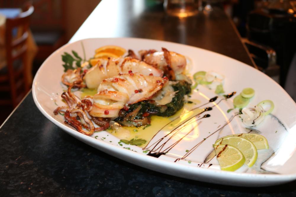 Tintenfischtube vom Grill auf einem Blattspinatbett und Parmesan, mit rotem Pfeffer, Olivenöl und leichter Säurenote