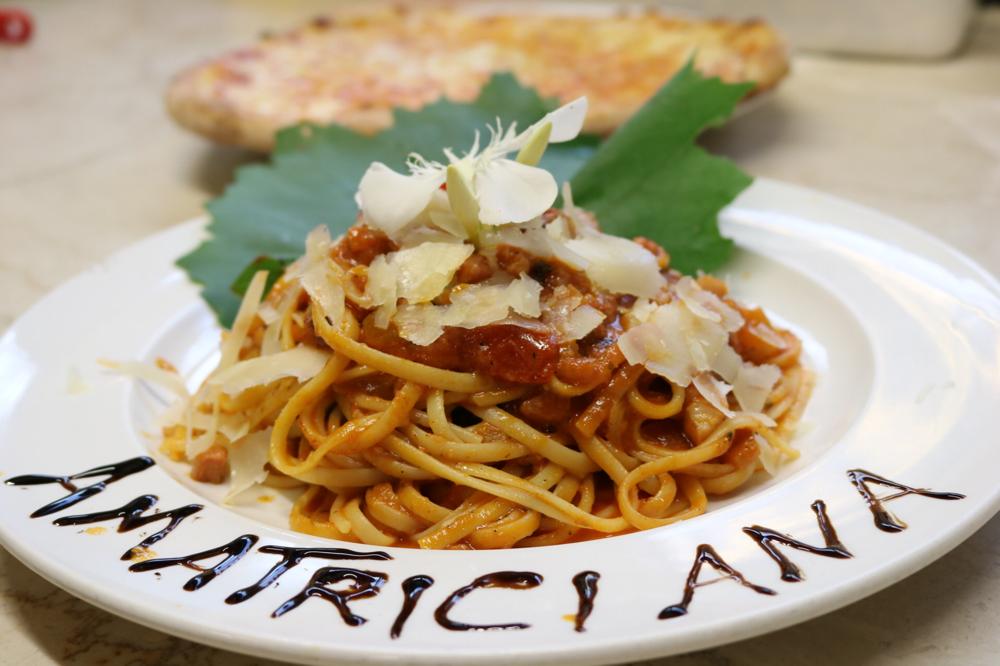 Linguini Amatriciana mit Speckwürfeln und Zwiebelstücken in hausgemachter Tomatensauce, mit sanfter Chilinote